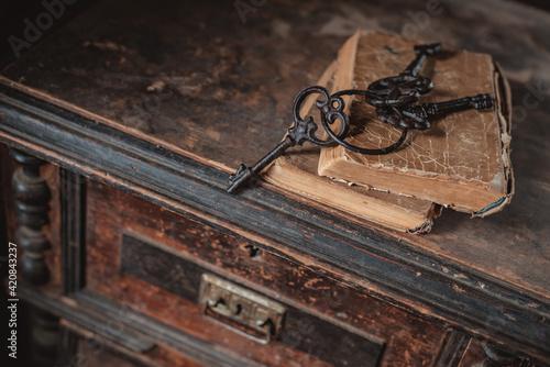 Fotografie, Obraz old vintage keys on an old battered book, antique wooden background