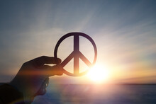 Peace Sign Symbol In The Hand Of A Man On The Background Of The Sunset.