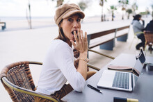 Surprised Young Woman Working Remotely  In Street Cafe