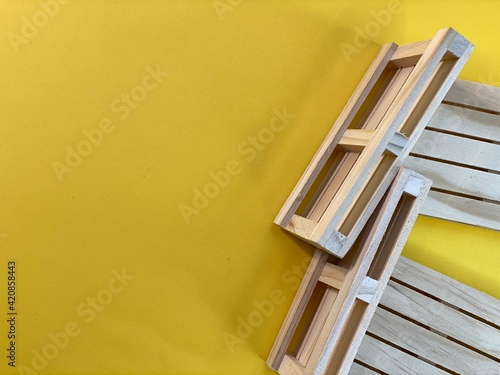 Fototapeta Wooden pallets are lying on a yellow background obraz