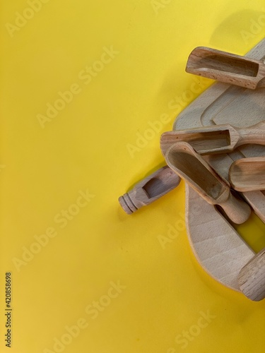 Fototapeta On a yellow background is a cutting board and wooden cutlery obraz