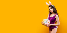 Attractive Hot Young Woman Wearing Bodysuit And Bunny Ears Holding Basket With Colored Easter Eggs While Posing On Yellow Background