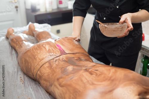 Fotografia Massage therapist smears the females body  with chocolate