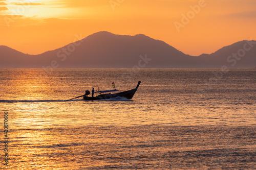 Obraz na plátně Ein Boot im Sonnenuntergang mit Bergen im Hintergrund