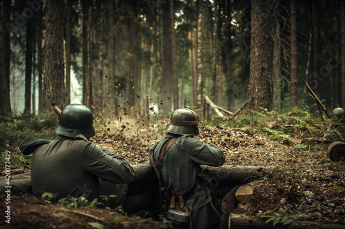 Fototapeta Finnish soldiers of the Second World War in helmets with guns in their hands, shoot back from the enemy in wooden trenches in the forest