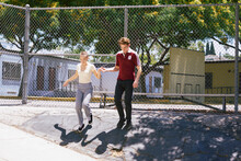 Young Man Giving Female Friend A Helping Hand In Park, Los Angeles, California, USA