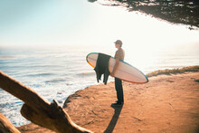 Young Man With Surfboard On Beach, Morro Bay, California, United States