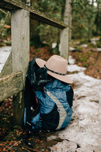 Hat And Backpack Leaning On Wood Structure In Forest