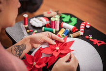 Woman Stitching Felt Poinsettia Onto Christmas Decoration, Over Shoulder View