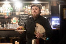 Man With Plate Of Burger And Menu In Pub