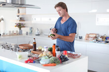 Mid Adult Man Preparing Food At Kitchen Counter