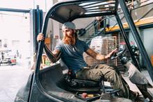 Man Reversing Fork Lift Out Of Warehouse