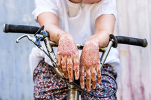 Woman With Henna Tattoo On Hands Sitting On Bicycle