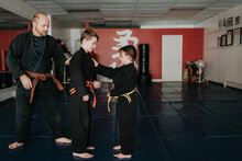 Coach And Students Practising Martial Arts In Studio