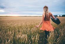 Woman Swinging Suitcase In Wheat Field, Edmonton, Canada