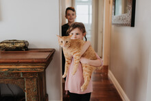 Boy Watching Sister Carrying Cat At Home