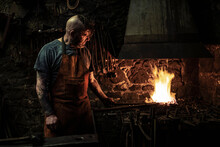 Mature Male Blacksmith Heating Metal On Open Fire In Workshop