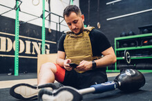 Man With Prosthetic Leg Sitting On Gym Floor Texting