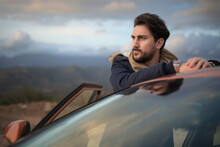 Man Resting Against Car On Roadside, Enjoying View On Hilltop