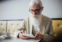 Senior Businessman Using Digital Tablet In Cafe
