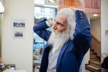 Senior Businessman Combing Hair In Salon