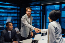 Businessman And Female Client Shaking Hands Over Conference Table Meeting