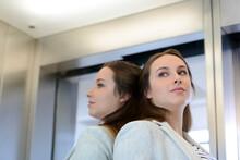 Businesswoman Daydreaming Inside Elevator