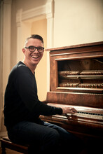 Man Grinning And Playing Piano