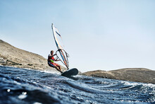 Young Man Leaning Back Windsurfing Ocean Waves, Surface Level View, Limnos, Khios, Greece