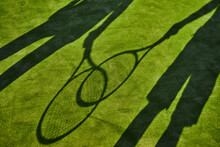 Cropped Shadows Of Two Tennis Players With Tennis Rackets On Green Lawn
