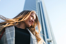 Young Woman With Long Blond Hair In Front Of Skyscraper, Low Angle View, Turin, Piemonte, Italy