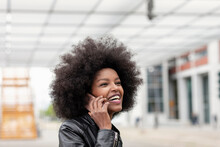 Young Woman With Afro Hair At City Train Station, Making Smartphone Call