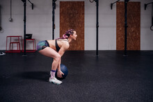 Young Woman Training, Lifting Atlas Ball In Gym