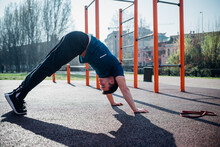 Calisthenics At Outdoor Gym, Young Man In Downward Dog Yoga Pose