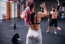Young Woman And Man Training, Lifting Dumbbells In Gym