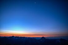 Orange Glow On Horizon Over Mountain Range, Saas-Fee, Valais, Switzerland