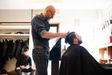 Hairdresser Combing Customer's Hair In Barber Shop