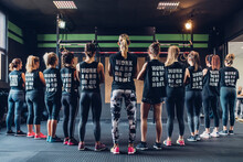 Group Of Women Training In Gym, Wearing Slogan T-shirts, Rear View