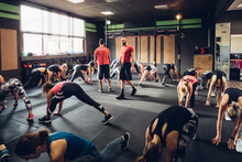 Large Group Of Women Training In Gym With Male Trainers, Bending Forward With Legs Outstretched