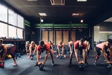 Women Training In Gym With Male Trainers, Preparing To Lift Kettle Bells