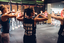 Group Of Women Training In Gym, With Arms Raised
