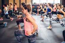 Group Of Women Training In Gym, With Hands On Hips And Legs Outstretched