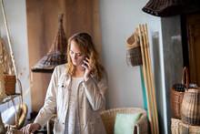 Young Female Basket Maker Making Smartphone Call In Workshop