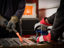 Knife Factory Workers Using Tongs To Remove Red Hot Metal From Mould In Workshop, Close Up Of Hands
