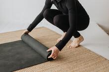 Woman Rolling Yoga Mat In Studio