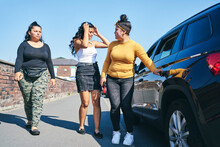 Young Woman And Two Teenage Sisters Opening Car Door, UK