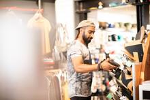 Man Choosing Skateboard In Shop