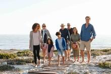 Family Of Eight Taking Walk On Beach