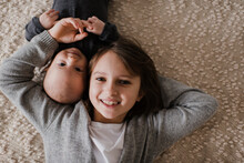 Girl Lying Cheek To Cheek With Baby Brother On Bed, Overhead Portrait