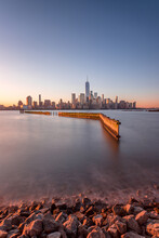 View Across The Water Of New York City, Manhattan Island, At Dawn, Flat Calm Water.